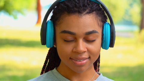 portrait attractive student friendly with earphones in park Live Action