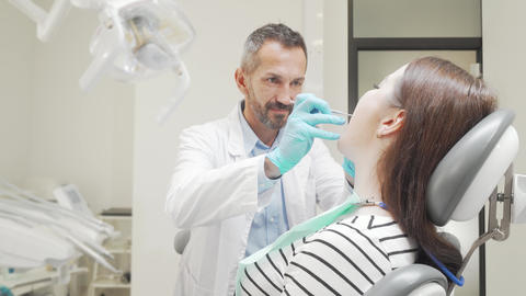 Cheerful young woman smiling to the camera after dental checkup Live Action