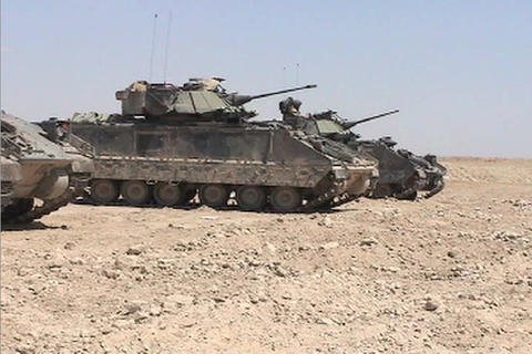 A line of American army tanks sits awaiting combat operations in the Iraqi desert Footage