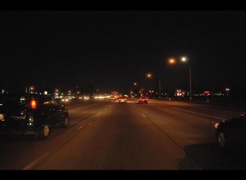 Traffic drives along a coastal city street at night Footage