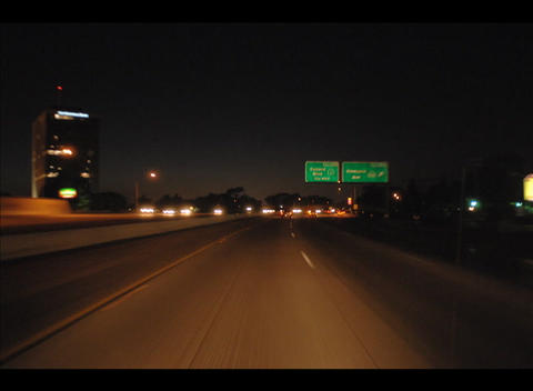 Traffic drives along a coastal city street at night Stock Video Footage