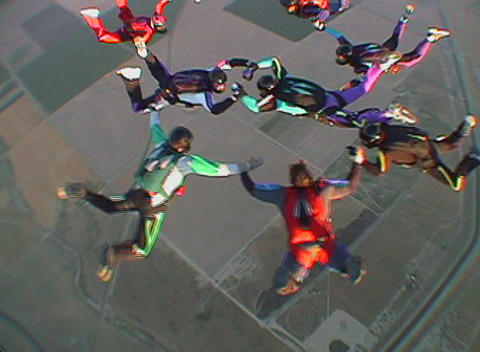 Nine skydivers maneuver in formation and disperse Live Action