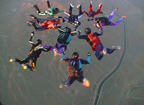 Nine skydivers maneuver in formation and disperse Stock Video Footage