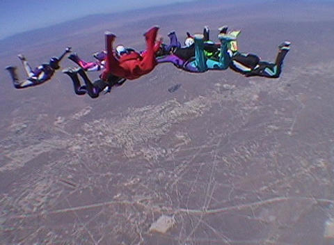 Ten skydivers free fall in a circle and disperse Stock Video Footage