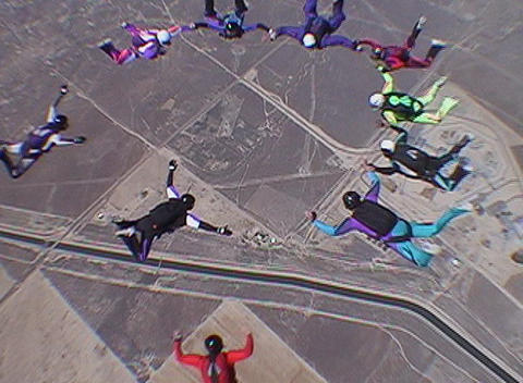 Ten skydivers free fall in a circle and disperse Footage