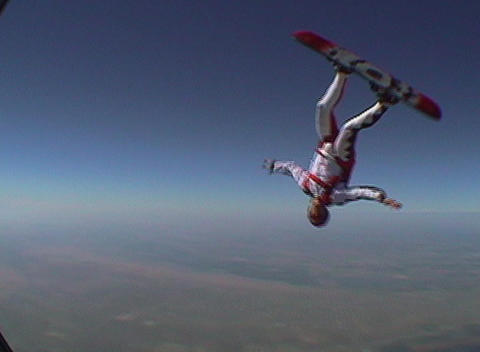 A skydiver jumps from an airplane and performs skyboarding maneuvers Footage