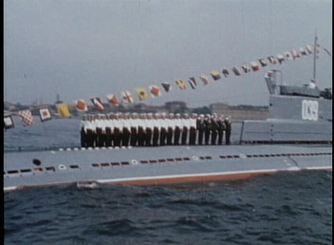 Russian Navy sailors stand on a submarine and salute at a military gathering in the 1970's USSR Footage