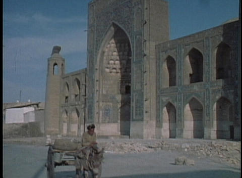 A man rides a donkey past a gate in Samarkand Footage