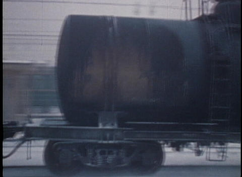Oil tanker cars pass on a freight train moving through the snow in this archival shot Footage