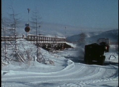Long haul trucks move through the snow in this archival shot Stock Video Footage