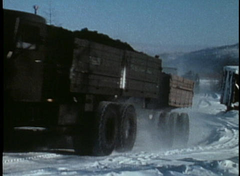 Long haul trucks move through the snow in this archival shot Footage
