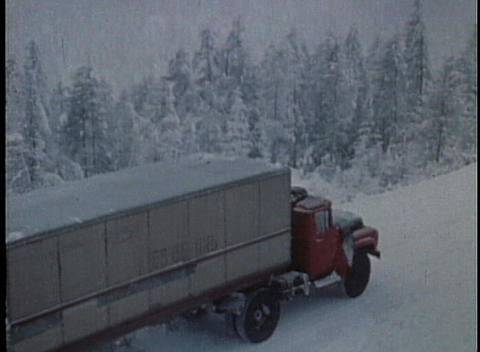 An old truck moves along a snowy road in this archival shot Footage