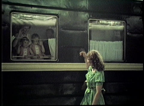 A woman waves goodbye to her children aboard a train in this archival shot Footage