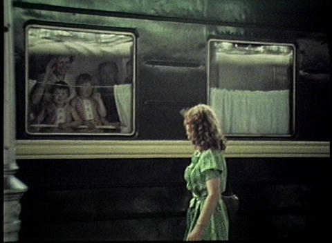 A woman waves goodbye to her children aboard a train in... Stock Video Footage