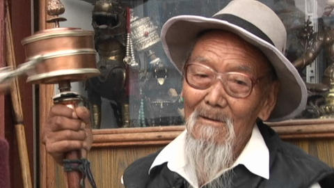 Tibetan old man spinning handheld prayer wheel in Kathmandu Stock Video Footage