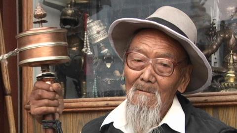 Tibetan old man spinning handheld prayer wheel in Kathmandu Footage
