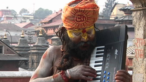 Hindu Sadhu - (Holy man) playing a keyboard at Pashupati... Stock Video Footage