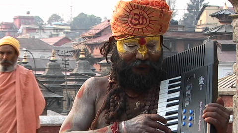Hindu Sadhu - (Holy man) playing a keyboard at Pashupati Temple in Kathmandu Footage