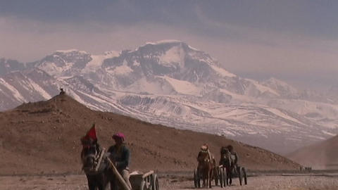 Tibetan man riding in carriage pulled by horse across the Tibetan Plateau with Mt. Cho Oyu in the ba Footage