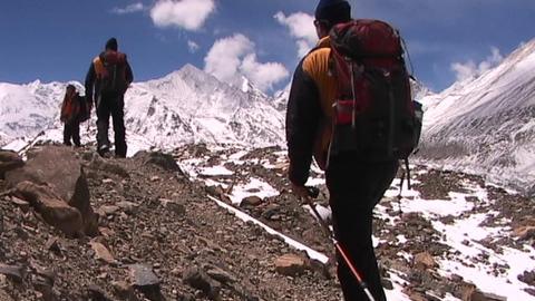 Climbers walk into panoramic Himalayan background Stock Video Footage