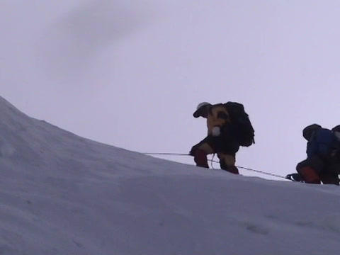 A team of climbers cross an ice ridge on Mt.  Everest Footage