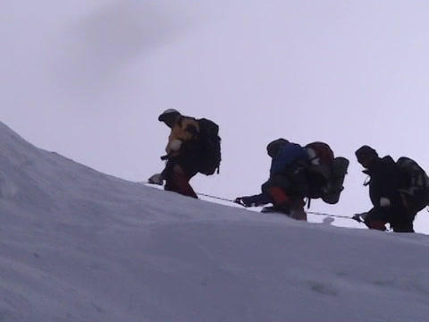 A team of climbers cross an ice ridge on Mt.  Everest Stock Video Footage