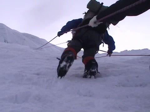 Climbers pulling themselves up on an icy slope Stock Video Footage