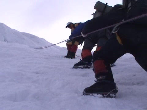 Climbers pulling themselves up on an icy slope Footage