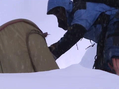 A climber opens up his tent high on Everest Stock Video Footage