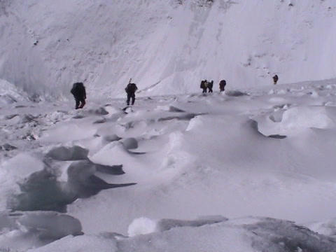 Climbers walk across a snow field off in the distance Stock Video Footage