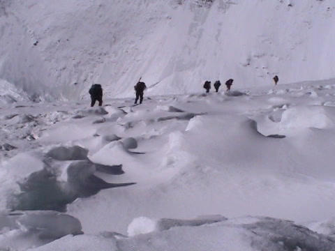 Climbers walk across a snow field off in the distance Footage