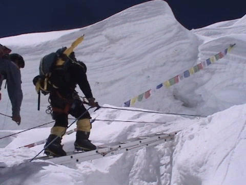 Climbers walking on a ladder over crevasse on Mt. Everest Footage