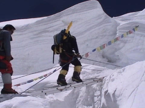 Climbers walking on a ladder over crevasse on Mt. Everest Stock Video Footage