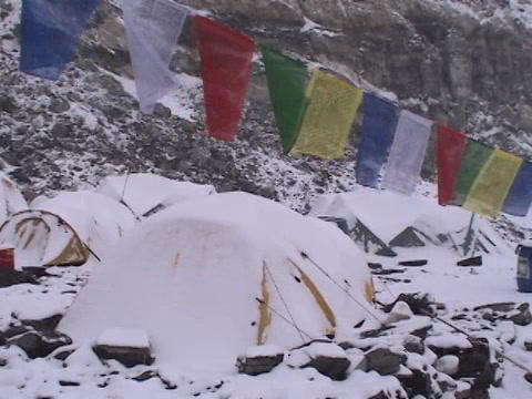 Snow falling on a tent with prayer flags blowing in the wind Stock Video Footage