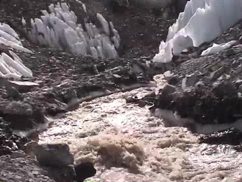 Mountain stream water running through an ice field Stock Video Footage