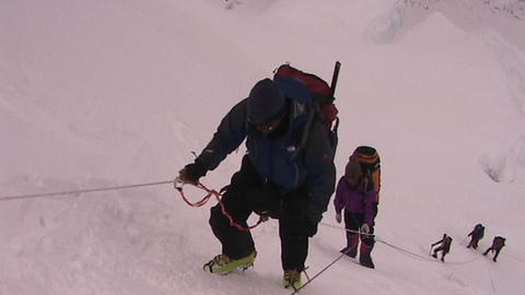 Exhausted climber pauses as he ascends an icy and steep... Stock Video Footage