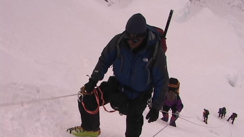 Exhausted climber pauses as he ascends an icy and steep slope Footage