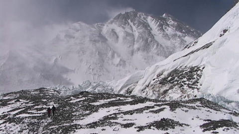 Climbers walking in the distance with Mt. Everest pinnacles and summit in the background Footage
