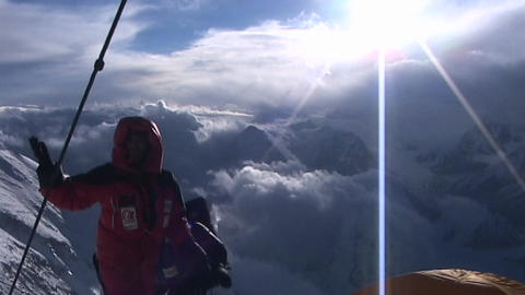 Climbers next to tent high on Everest look around at scenery Stock Video Footage