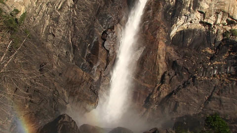 A rainbow forms near the bottom of a cascading waterfall Footage