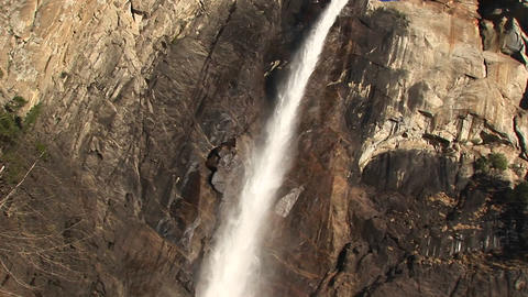 A rainbow forms near the bottom of a cascading waterfall Stock Video Footage