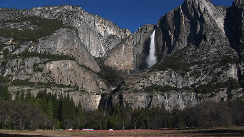 Rocky mountains feature a waterfall and traffic at the base of the mountains Footage