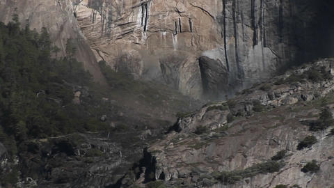 The camera pans upward and right from a small waterfall in rugged mountains to a larger one above it Footage