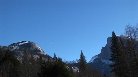 Pan-left across Yosemite mountain peaks to Yosemite Falls... Stock Video Footage