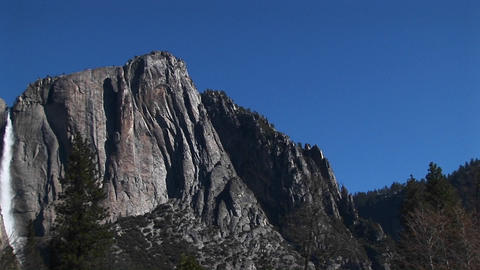 Pan-left across Yosemite mountain peaks to Yosemite Falls in Yosemite National Park, California Footage