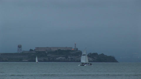 A catamaran glides by historic Alcatraz Prison on a foggy... Stock Video Footage