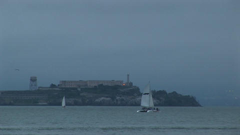 A catamaran glides by historic Alcatraz Prison on a foggy day Footage