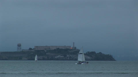 Medium shot of a catamaran moving past historic Alcatraz island opposite San Francisco Footage