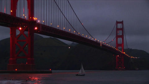 A worms-eye view of the Golden Gate Bridge at night with its lights reflecting on the water Footage