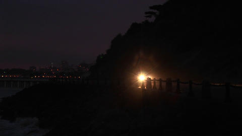A car's headlights brighten a dark road on the far side... Stock Video Footage